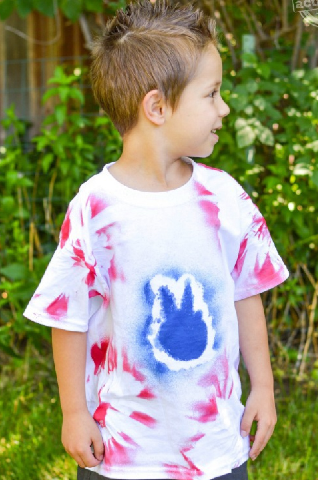 Boy in a red, white, and blue tie-dye shirt with a leafy background.