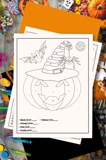 halloween coloring pages addition color by number worksheet on a desk surrounded by Halloween themed art and craft supplies