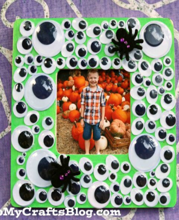 Halloween frame that is green and covered in all sized of googly eyes and small plastic spiders