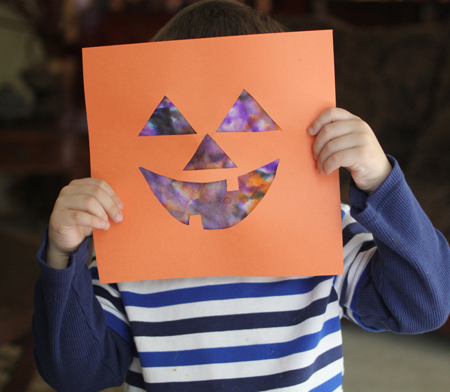 Kid in a blue and white striped shirt holding a jack-o-lantern paper craft up to their face.
