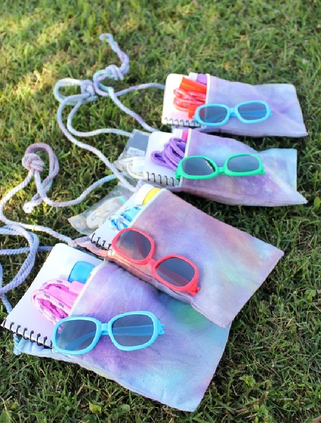 Four tie-dye party favor bags full of sunglasses and notebooks on grass.