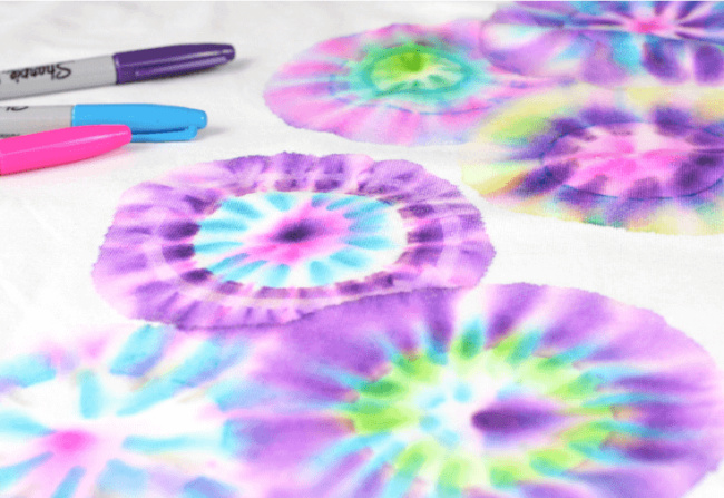 Tie-dye circles on white fabric with permanent markers in background.