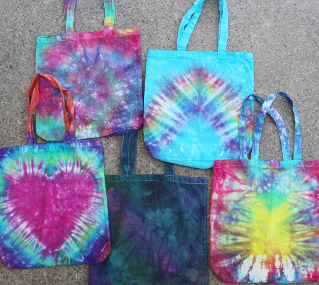 Five different colored tie-dye tote bags laid out on the ground.