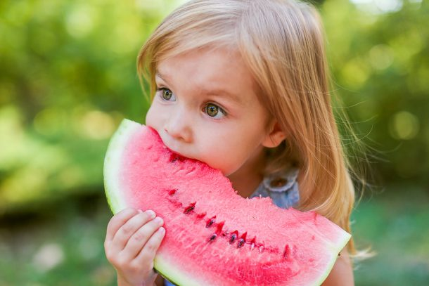 Healthy snacks will help kids feel fuller longer as you can see with this little blonde girl eating a big chunk of watermelon