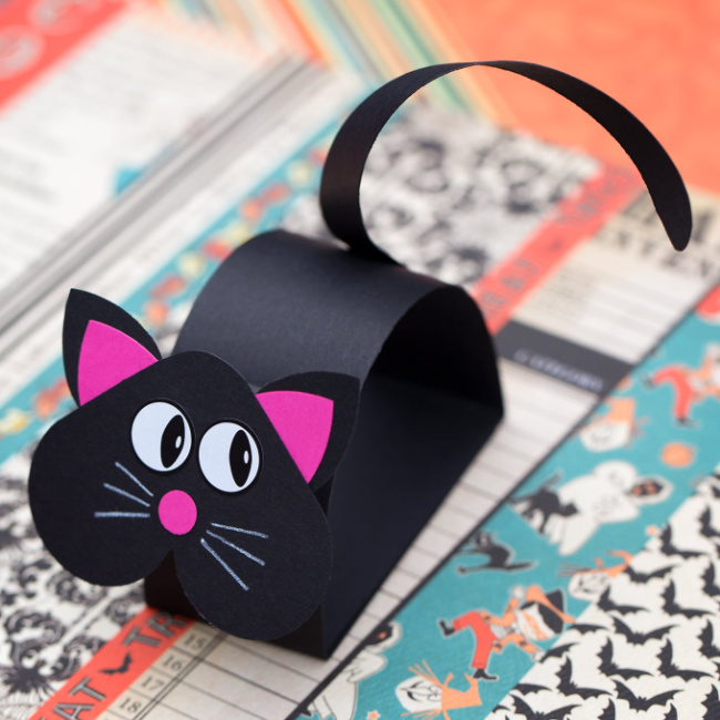 Black cat paper craft on a printed background.