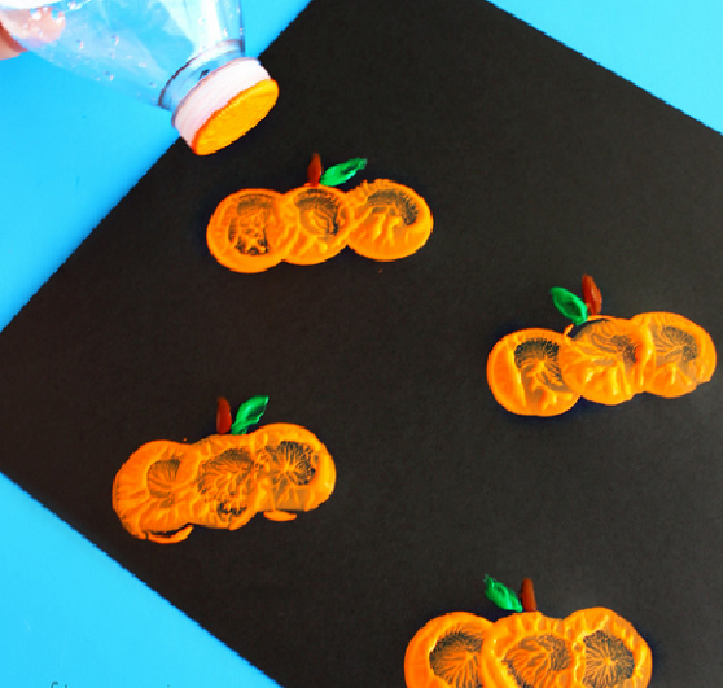 Bottle cap in orange paint stamping a black paper set on a blue background to create pumpkin shapes.