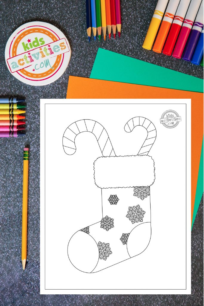 Print and color this Christmas candy cane coloring page! Coloring page of a snowflake-decorated Christmas stocking on a desktop surrounded by brightly colored crayons, markers, and coloring pencils.