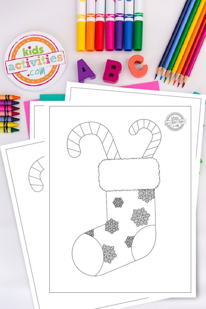 Print and color this Christmas candy cane coloring page! This sweet printable is fun, festive, and will get your kids in the holiday spirit. Coloring page of a snowflake-covered Christmas stocking with candy canes on a white desktop surrounded by colorful art and craft supplies.