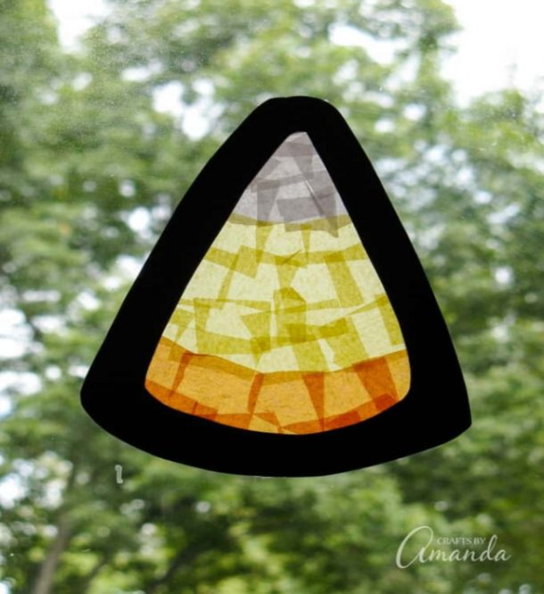 candy corn crafts made with double sided contact paper with squares of orange, white, and yellow tissue paper with a black outline.
