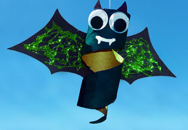 Toilet paper roll decorated bat with sparkly green wings hanging over a blue background.