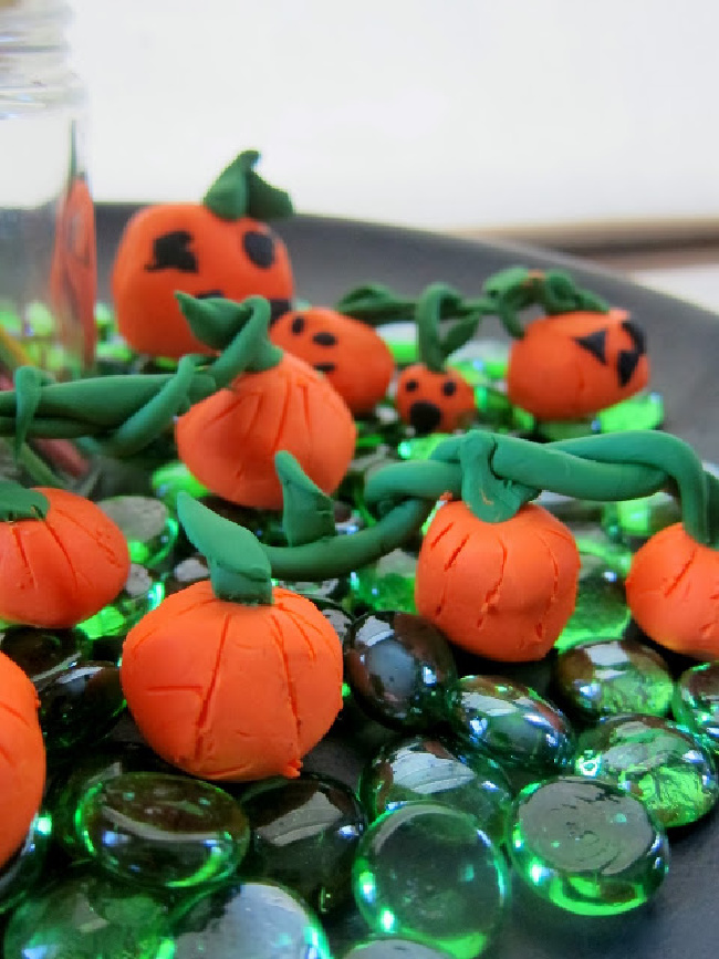 Small clay pumpkins resting on green glass jewels on a table.