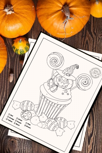Halloween color by number activity printables, showing the worksheet with a cupcake that has a jack o lantern with witch hat cupcake topper surrounded by trick or treat candy and an eyeball. Printable is on a wooden tabletop surrounded by Halloween decorations and craft supplies
