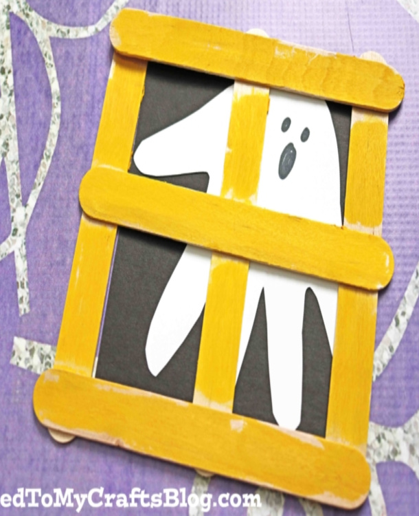ghost in the window craft with yellow popsicle sticks. The background is black with a white handprint as a ghost