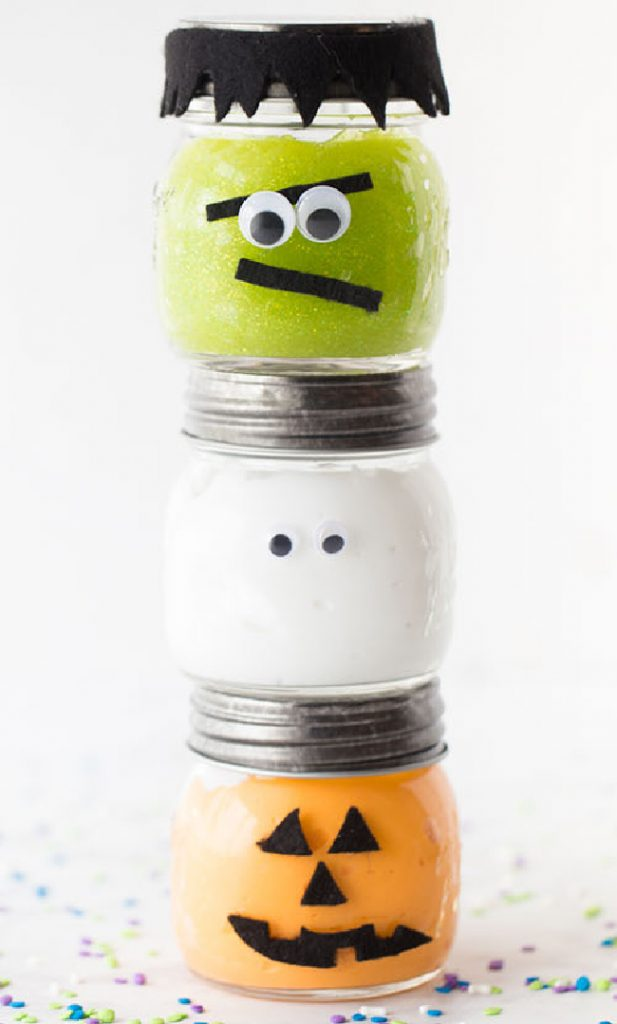 Glass containers of Halloween slime, a green Frankenstein slime stacked on a white ghost slime, which is stacked on an orange pumpkin slime.