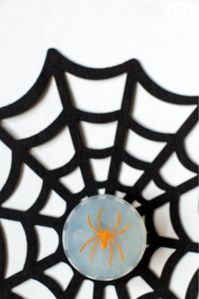 Clear soap with an orange spider in the middle resting on a black felt spider web on a white background.
