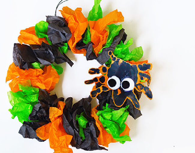 Halloween wreath made of green, black and orange tissue paper with a black spider on the right side, set on a white background.