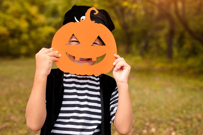 A boy wearing a pirate costume is holding an orange paper pumpkin mask in front of his face while smiling.