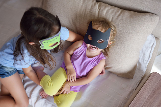 Two girls are sitting on a couch and each has a Halloween paper mask on their face. The girl looking at the camera is wearing a batgirl mask and she has a huge smile on her face.