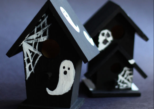 Mini wooden haunted houses painted black with white ghosts and spiderwebs.