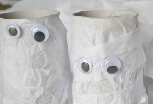Mummy craft made out of toilet paper rolls with googly eyes.