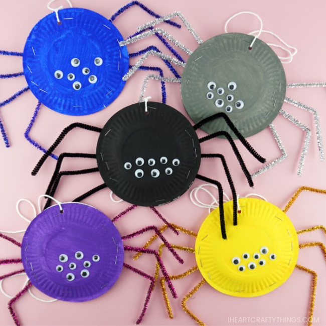 Five paper plate spiders in the colors blue, gray, black, purple, and yellow on a pink background.