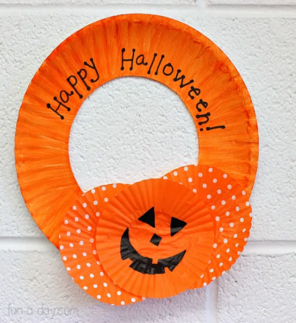 paper plate wreath craft that is orange, says Happy Halloween, and has orange and white cup cake liners and an orange jackolantern cupcake liner.