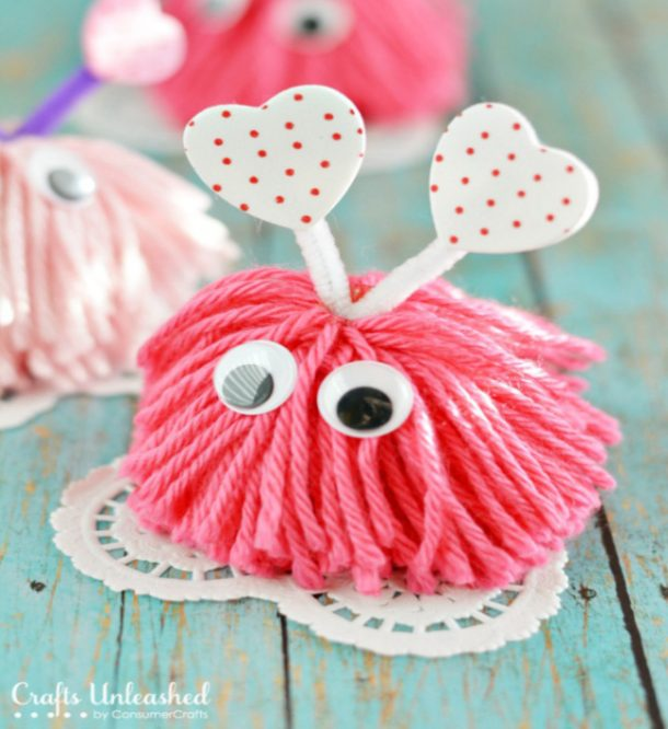 pom pom monster crafts that are pink, with googly eyes, with white doilies beneat them and white and red heart antennas