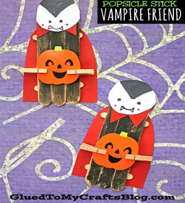 popsicle stick vampire with a popsicle stick body, a red cape and collar, holding a jackolantern with black hair