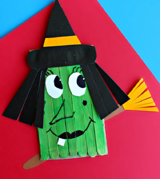 Popsicle green witch craft with a broom and witch hat on a red paper and blue background.