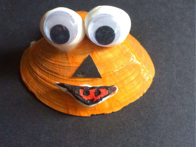Seashell painted orange with pumpkin eyes, nose, and mouth on a black background.