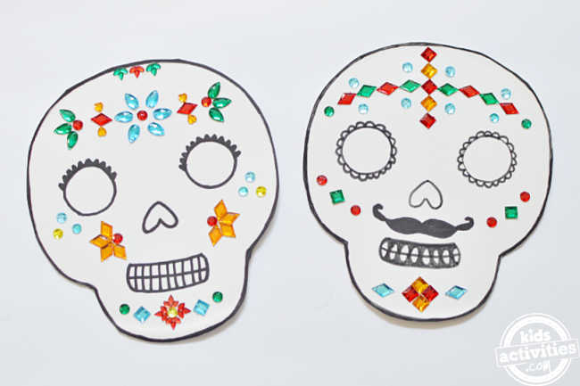 Two paper plate masks embellished with rhinestones for the day of the dead