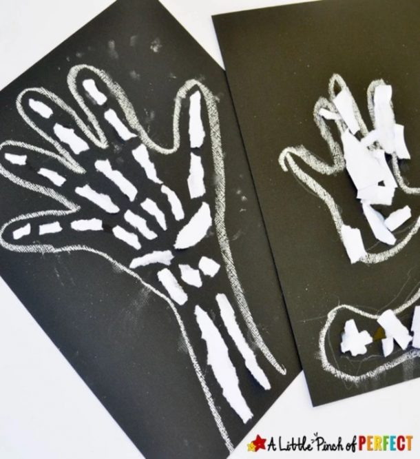 skeleton craft on black construction paper outlined in white chalk and the hand and arm is filled with torn white paper to look like bones