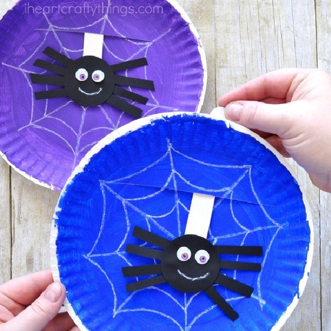 Purple and blue painted paper plates with spider webs painted on and a black spider sticking through the middle of them.