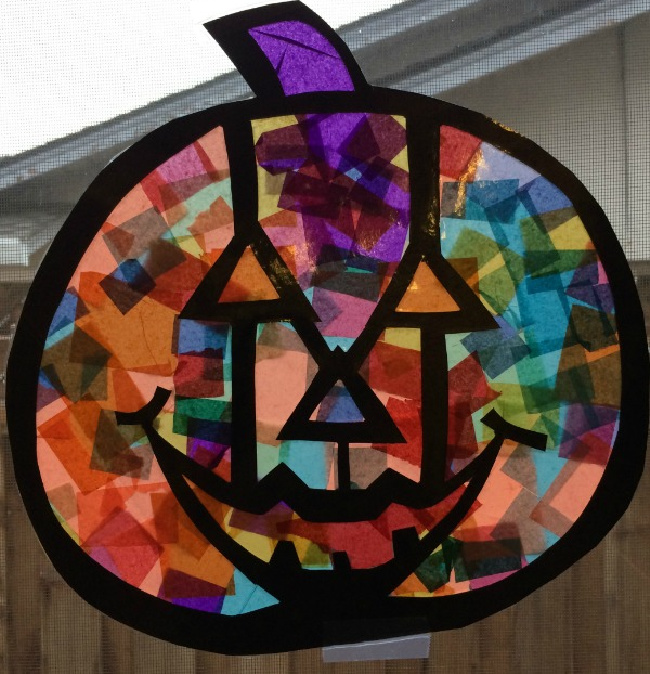 Stain glass pumpkin, made of many colors with a jack-o-lantern face.