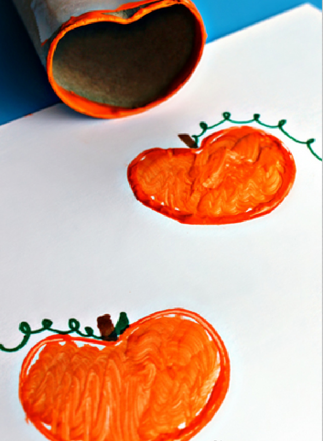 Toilet paper roll with orange paint on edge stamping pumpkins onto a white paper.