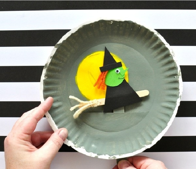 Paper plate flying witch craft being held by someone over a black and white striped background.
