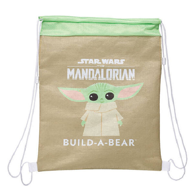 "Baby Yoda Build-A-Bear brown bag carrier with a green top and Baby Yoda in the center of it with the words ""Star Wars The Mandalorian Build-A-Bear"" surrounding it."