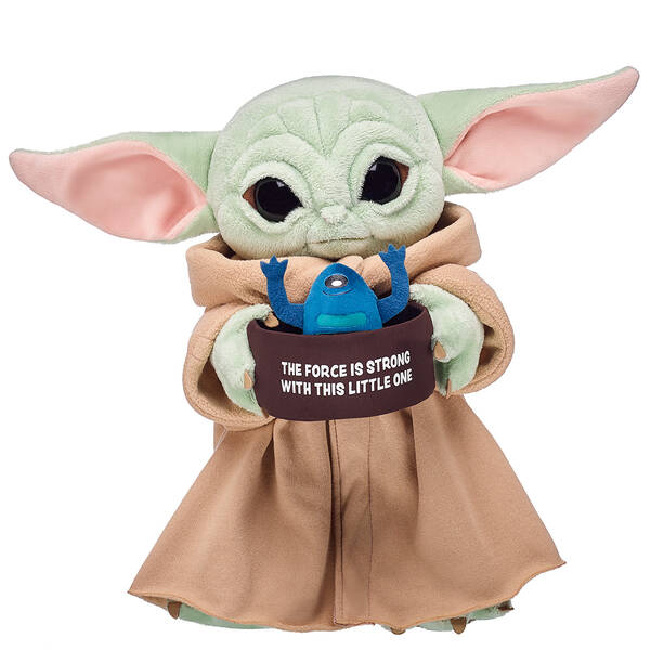 "Baby Yoda Build-A-Bear in brown robe holding a soup bowl that says ""The Force is Strong With This Little One"" with a blue frog sticking out of it."