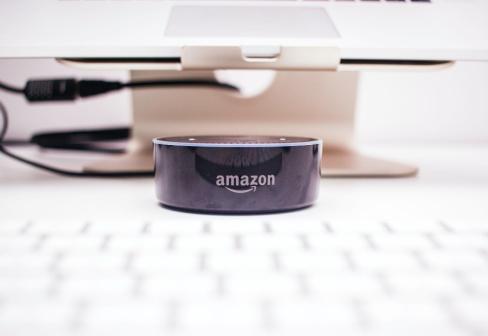 older Amazon Product (Looks to be an echo) sits between a computer monitor stand and the keyboard