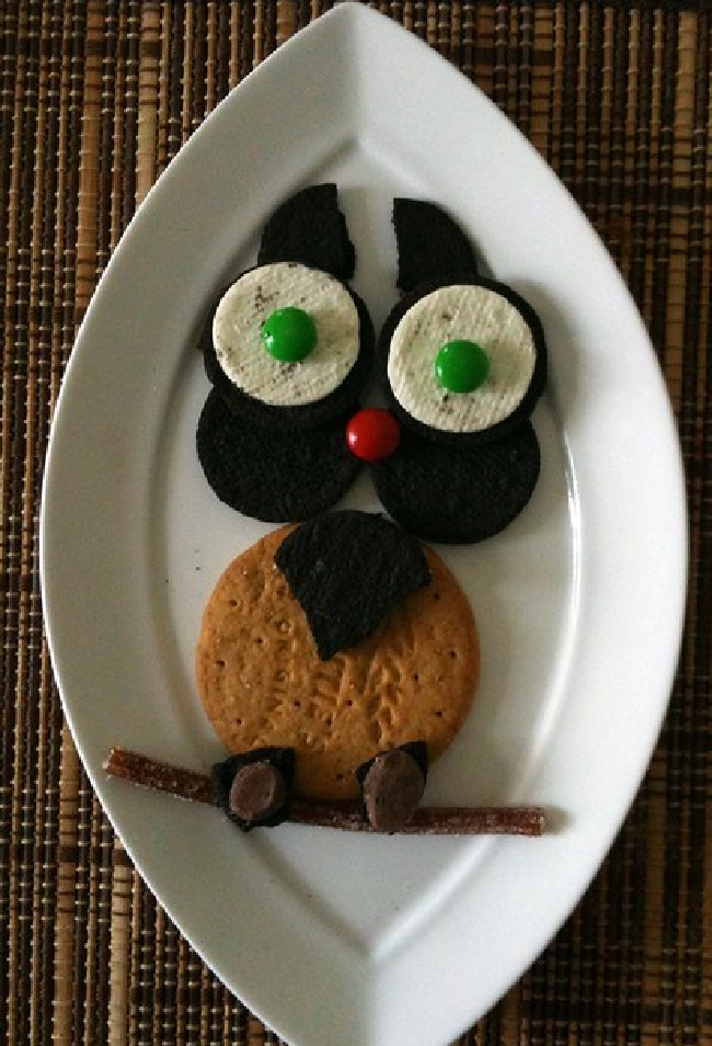 Edible owl treat made of cookies, candy, and pretzels on a diamond-shaped white plate.