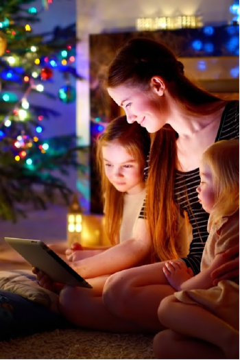 Mother shows her two children hallmark movies on an iPad, in front of a christmas tree