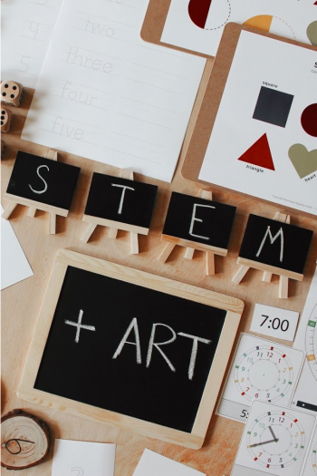 "The words ""STEM + Art"" are written on small chalkboards. They are surrounded by various learning activities and printed practice pages."