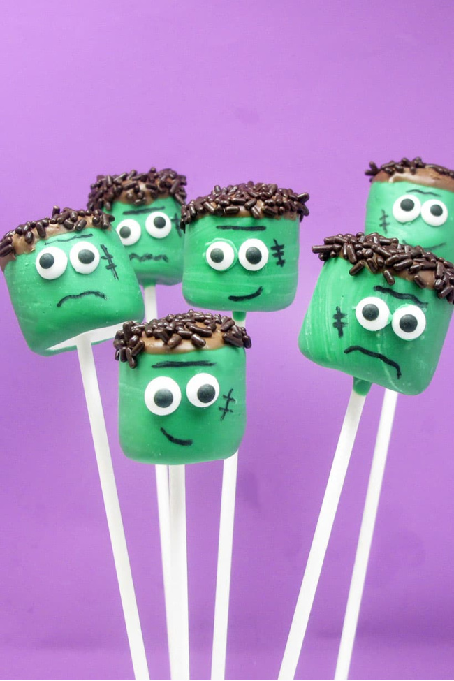 Green Frankenstein marshmallows on white sticks in front of a purple background.