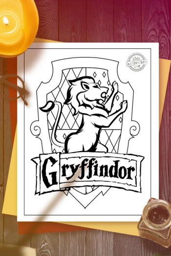 Gryffindor crest coloring page on red and yellow construction paper on a wooden surface with candle, inkpot and quill, Harry Potter glasses and shadow of someone waving a magic wand