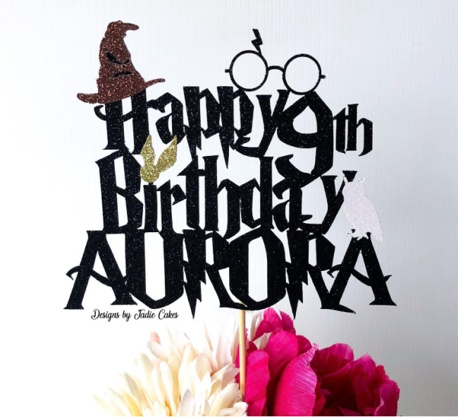 Harry Potter birthday cake topper on top of white and pink flowers, with the words Happy 9th Birthday Aurora, with a sorting hat and round glasses on top.
