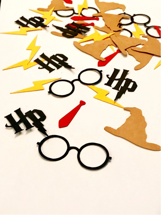 Harry Potter confetti of sorting hats, HP letters, round glasses, red ties, and lightning bolts on a white table.