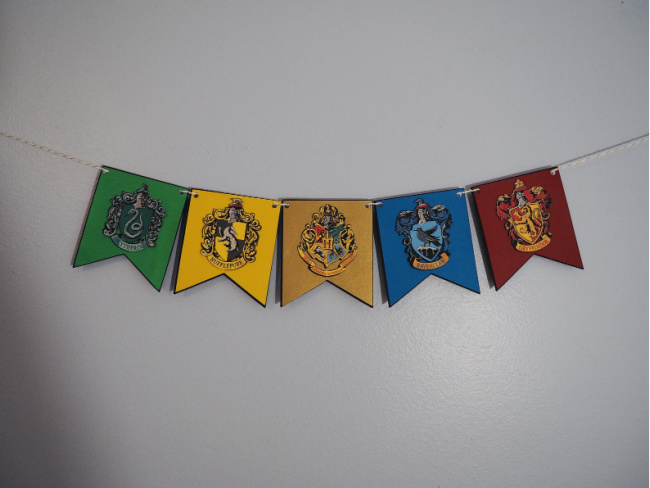 Harry Potter House crest banner hanging on a white wall with the houses Slytherin, Hufflepuff, a Hogwarts crest, Ravenclaw, and Gryffindor.
