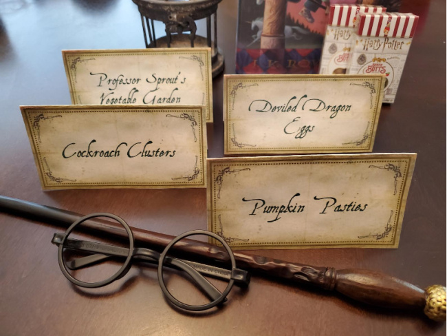 Harry Potter food label card that say Professor Sprout's Vegetable Garden, Deviled Dragon Eggs, Cockroach Clusters, and Pumpkin Pasties. Set on a wooden table with a wand and round glasses set in front of them and Harry Potter jelly beans behind them.