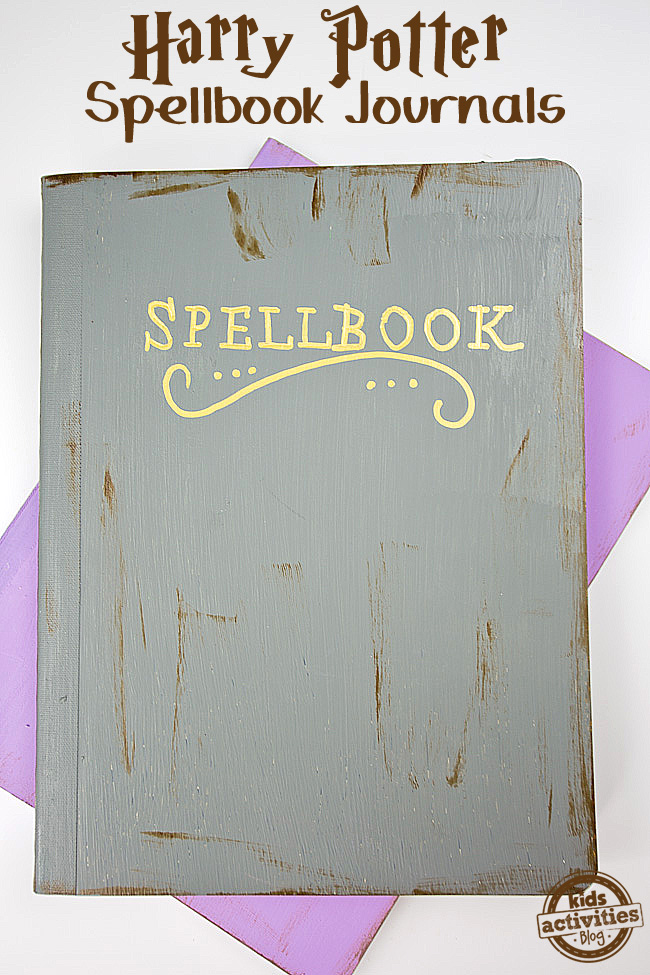 Harry Potter gray spellbook journal on top of a purple journal on a white background