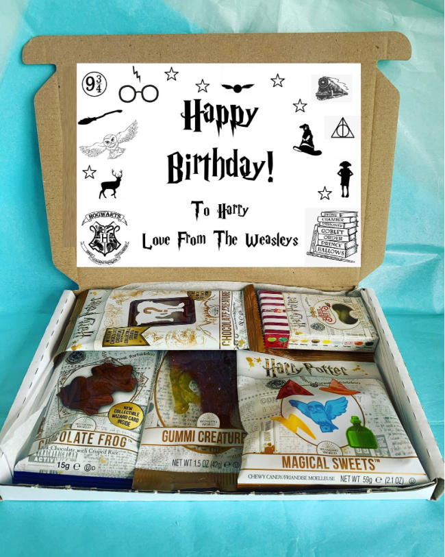 Harry Potter sweets gift box. An open cardboard box with Harry Potter treats inside like chocolate frogs, jelly beans, and gummies. A paper that says Happy Birthday, To Harry, Love From The Weasleys on the inside top of the box.